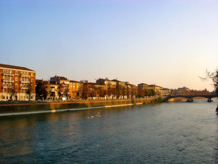 City and Adige River illuminated at sundown