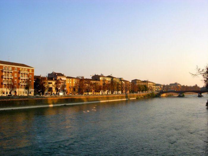 City and Adige River illuminated at sundown